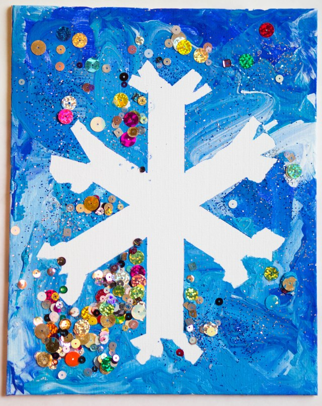 Just put painters tape on a canvas in the shape of a snowflake, use lots of different shades of blue paint and some white paint, let the munchkin paint away, add glitter or sparkles if you want, let dry half way, then peel off the tape.  Easy peasy!